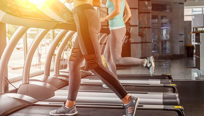 ランニングマシーンで体を鍛える女性