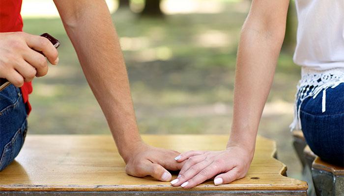 ベンチで手を重ねあう男女